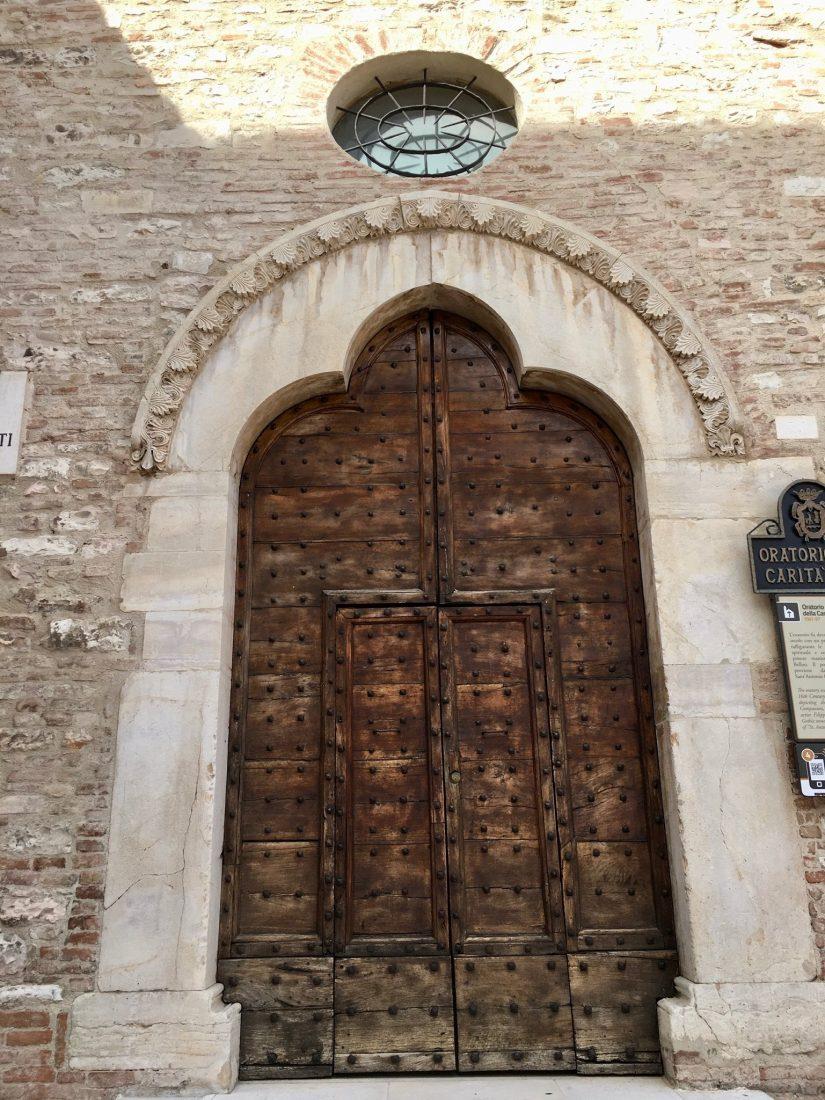 Holztür an einer Kirche in Fabriano