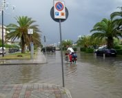 Radfahrer auf überschwemmter Strasse